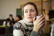 portrait of sad woman in sweater drinking coffee at cafe