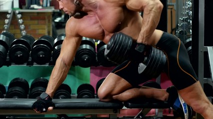 Muscular sportsman doing exercises on left hand with dumbbell in