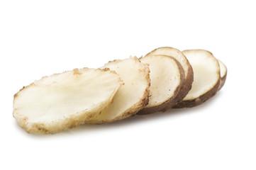 Topinambur, cut into slices on the white