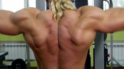 Back view of bodybuilder doing exercises on the trainer, close