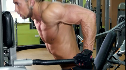 Muscular sportsman doing exercises for his hands in the gym