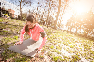 Young Woman Doing Push-Ups Exercises at Park.