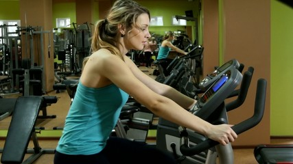 Attractive, sporty girl is cycling in fitness gym