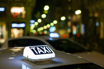 Taxi sign from parked taxi in the Milan street at night.