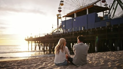 romantic couple watching sunset at santa monica