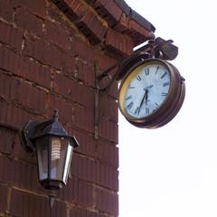 old clock and lamp on  brick wall