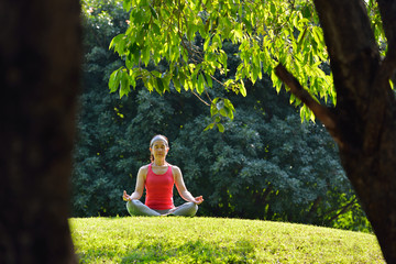 Middle aged woman doing yoga posture outdoor
