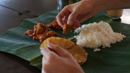 man eats food with hands from banana leaf