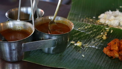 man pours out dressings onto Indian food on banana leaf