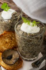 Mushroom pate in a jar over dark background, selective focus,