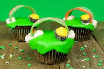 St Patricks Day cupcakes on wood with green background