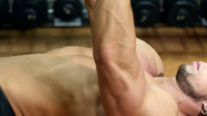 Side view sportsman doing exercises with dumbbell in the gym