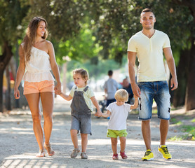 Young parents with children holding vacation in park