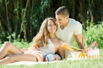 Happy  romantic couple sitting  at picnic