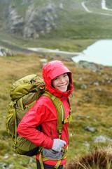 Hiker woman hiking with backpack in rain on trek