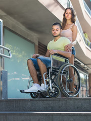 Upset wife with man in wheelchair on stairs