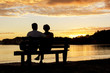 Leinwanddruck Bild - Couple watching a beautiful sunset together