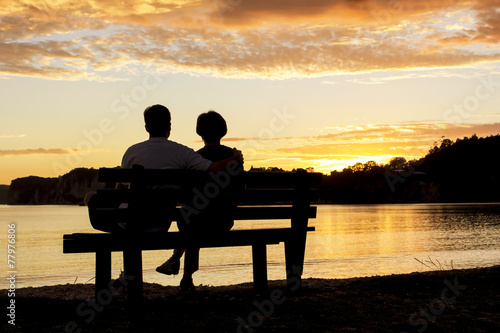Leinwanddruck Bild Couple watching a beautiful sunset together
