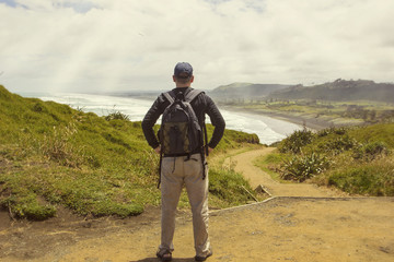 Male hiker looking at a beautiful ocean view in New Zealand