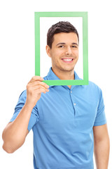 Man posing behind a green picture frame