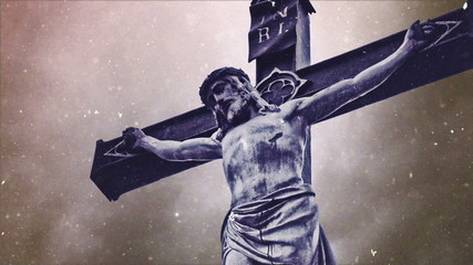 Crucifixion cross with Jesus Christ statue over stormy clouds