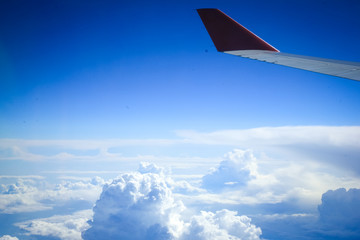 Wing of an airplane in beautiful sky with clouds