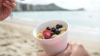 Acai bowl - girl eating healthy food on beach