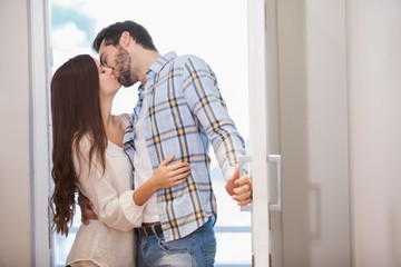 Young couple kiss as they open front door