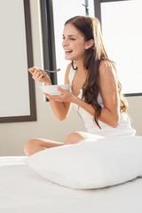 Smiling pretty brunette having breakfast in bed