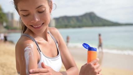 Sunscreen fitness woman applying suntan lotion