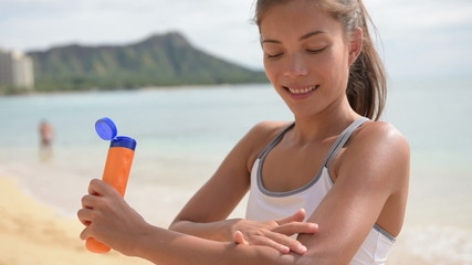 Fitness woman applying sunscreen suntan lotion