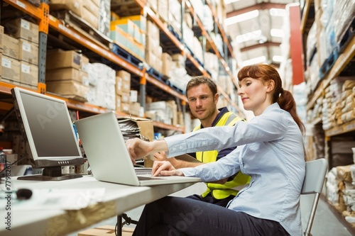 Warehouse worker and manager looking at laptop - 77982617