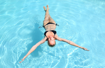Beautiful Caucasian lady floating in swimming pool.