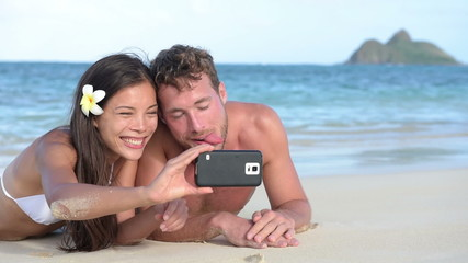 Beach couple taking funny selfie with smartphone