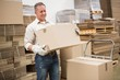 Worker carrying box in warehouse - 77984234