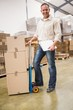 Delivery man leaning on trolley of boxes