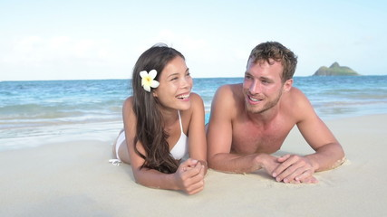 Vacation couple laughing relaxing on beach tanning