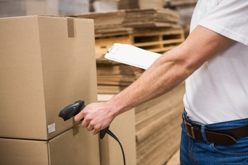 Worker using scanner in warehouse