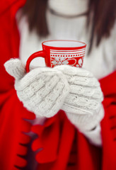 the girl in mittens holds a red cup in hand