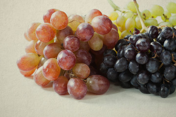 Red, green and purple grapes on a vintage paper background.