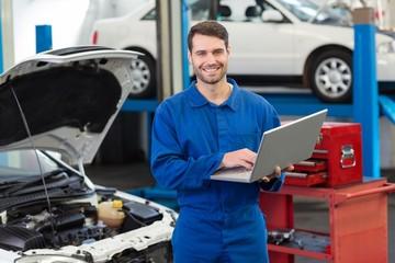 Smiling mechanic using his laptop