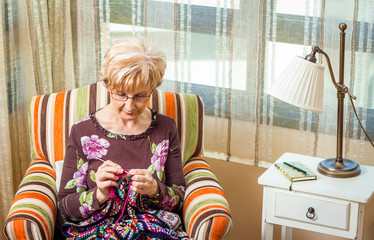 Senior woman knitting a wool quilt with patches