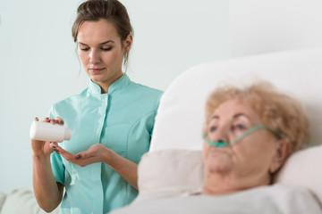 Ill senior woman and nurse