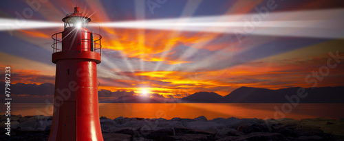 Red Lighthouse with Light Beam at Sunset - 77987233