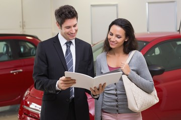 Salesman showing brochure to customer and smiling