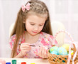 Little girl painting colorful easter eggs