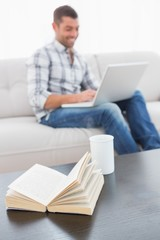 A man writing on a computer sitting on a sofa