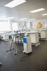 Empty class room with ironing board