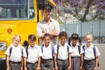 Cute pupils with their school bus driver