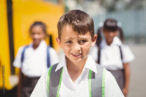canvas print picture Cute pupil smiling at camera by the school bus